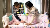 cosiness : Young parents in stylish sweaters bent over baby crib
