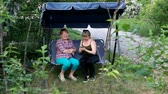 snění : two women are sitting on a garden swinging and talking to each other