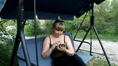 snění : a woman sits on a garden swing and controls a smartphone
