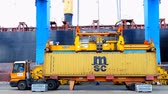 crane : International Container ship unloading containers on service trucks Stock Footage