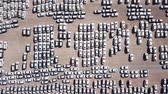 zvětralý : New cars covered in protective white sheets parked in a holding platform - Aerial footage