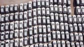 New cars covered in protective white sheets parked in a holding platform - Aerial footage