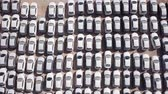 lote : New cars covered in protective white sheets parked in a holding platform - Aerial footage