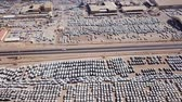 los : New cars covered in protective white sheets parked in a holding platform - Aerial footage