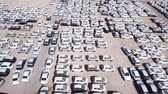 kész : New cars covered in protective white sheets parked in a holding platform - Aerial footage