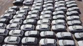 распределение : New cars covered in protective white sheets parked in a holding platform - Aerial footage