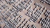 parked : New cars covered in protective white sheets parked in a holding platform - Aerial footage