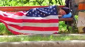 dakloze : View of a homeless man lying on bench covered with USA flag. Stockvideo