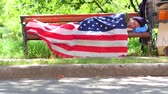 vício : Homeless man using USA flag as a blanket.