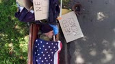 tramp : Top view of a beggar lying on bench, covered with flaf of USA.