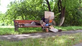 dakloze : View of homeless old man on the bench in city park.