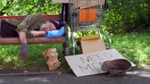 dakloze : View of drunk homeless man sleeping at day time on the bench in the street.