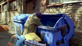 dakloze : Footage with homeless man searching food and empty bottles in garbage. Stockvideo