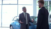 revendedor : Handsome man at auto showroom talking with vehicle dealer.