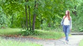 maravilha : Portrait of beautiful fashion girl walking on park path. Looking at trees. Free time concept. Stock Footage