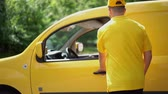 тележка : Attractive Woman Takes Caron Box From Delivery Man In Yellow Uniform. After Giving The Ordered Parcel To Excited Female Client The Courier Returns To His Yellow Van And Sits In Driver Seat Smiling,