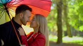 mladých dospělých : Close-up Of Lovely Couple Rubbing Noses While Standing Under Rainbow Umbrella. Slow Motion Of Attractive Woman Looking With Love At Her Handsome Husband. Under Rainbow Umbrella In The Park. Romance Concept