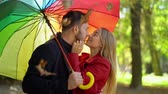 mladých dospělých : Slow Motion Of Cute Couple Rubbing Noses And Kissing Under Rainbow Umbrella. Falling Leaves And Charming Lovers On Their Date Stand Under Rainbow Umbrella Kissing.