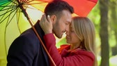 mladých dospělých : Passionate Couple Is Cuddling Up Together, Standing Under Rainbow Umbrella. Portrait Of Handsome Man Reaching To Kiss His Lovely Girlfriend Under Rainbow Umbrella. Dostupné videozáznamy