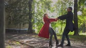 mladých dospělých : Happy Couple Holds Hands And Spins Around In The Park Under Bright Sunshine. Slow Motion Of Cheerful Man And Woman On Their Date Whirling In The Park. Dostupné videozáznamy