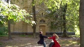 mladých dospělých : General Shot Of Beautiful Couple Spinning Around Holding Hands. Lovely Couple Spins In Front Of An Old Brick Building In The Park On Their Date In Slow Motion.