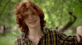 dromer : Charming Ginger Man Smiles At Camera. Portrait Of Young Guy With Wind Ruffling His Red Hair. Slow Motion