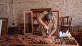 lumber industry : Carpenter Working With Drill In Old Workshop. Puts Together Items For Small Wooden Ship Figures. Carpentry Concept.