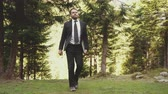 A Man In A Black Suit And White Shirt Is Walking Through The Woods. A Man Walks Through The Woods With A Laptop In His Hand. Business And Tourism Concept Video Videos