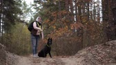 бросать : Woman Is Training Her Active Black Shepherd Dog. The Female Is Throwing Away A Stick And The Dog Runs To Catch It.
