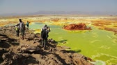 danakil : ETHIOPIA, DALLOL-CIRCA DECEMBER 2017 - unidentified people walking in the volcanic depression Stock Footage