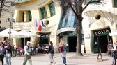 main street : Sopot, Poland - April 20, 2018: people walking near famous touristic attraction Crooked little house (Polish: Krzywy Domek) on Bohaterow Monte Cassino street. Stock Footage