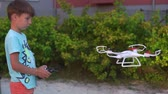 white quadrocopter takes off in front of the childs face 7 years Стоковые видеозаписи