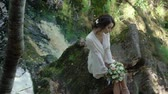 slowmotion : Young woman sitting on a rock near waterfall in lingerie Stock Footage