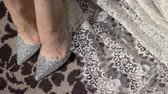 Bride sitting in wedding shoes indoors 動画素材
