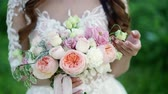пион : Young bride touching bridal bouquet in a park