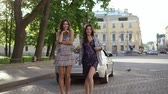 kupé : Two young woman posing near luxury sports car in a city