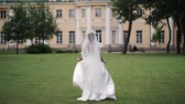 matrimoni : Young bride running in a park slowmotion waving dress and long veil at cloudy day