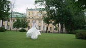 correção : Young bride running in a park slowmotion waving dress and long veil at cloudy day