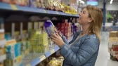 grocer : Woman shopping at the supermarket. Choosing food products in a shop Stock Footage