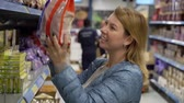 trolejbus : Woman shopping at the supermarket. Choosing food products in a shop Dostupné videozáznamy