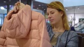tentação : Beautiful young women choosing clothes in shop. Blonde caucasian female in fashion store choosing and trying jacket Stock Footage