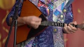 оркестр : Unrecognizable man in a folk shirt plays a balalaika on a stage at outdoors open-air concert