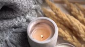 aconchegante : Cozy burning candles and gray knitted blanket in real room interior, winter home decoration