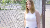 rozjímavý : pretty young woman standing near chain link fence
