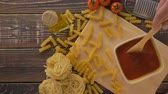 spagetti : Pasta and ingredients on the wooden table Wideo
