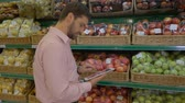 shopping bag sale : Man using tablet at fruit counter In supermarket Stock Footage