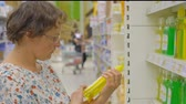 cheaper : woman buys cleaning products in a supermarket