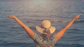 high up : Back view of woman with hands up over sea view at sunset time Stock Footage