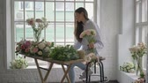 sale : Young florist girl counting bouquet cost using tablet at her flower studio