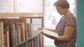 university : Woman reading book in library